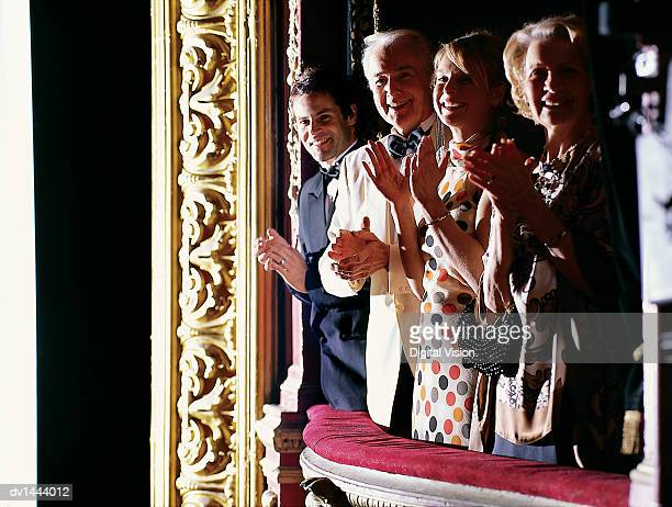 Mature and Young Couples Standing in a Theatre Balcony Applauding