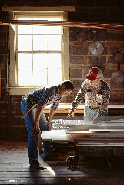 Mature and young men working in wood shop