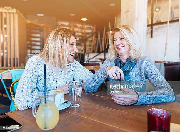 Mature and young woman having coffee time in modern cafe