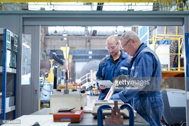 Mature and younger engineers inspecting turbine blade in turbine maintenance factory