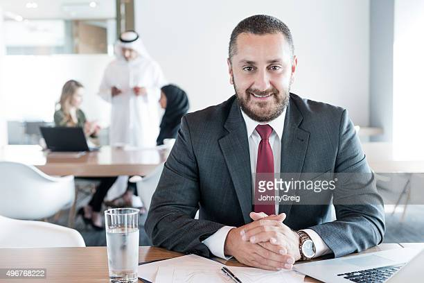 Mature Arab businessman at desk in office, portrait
