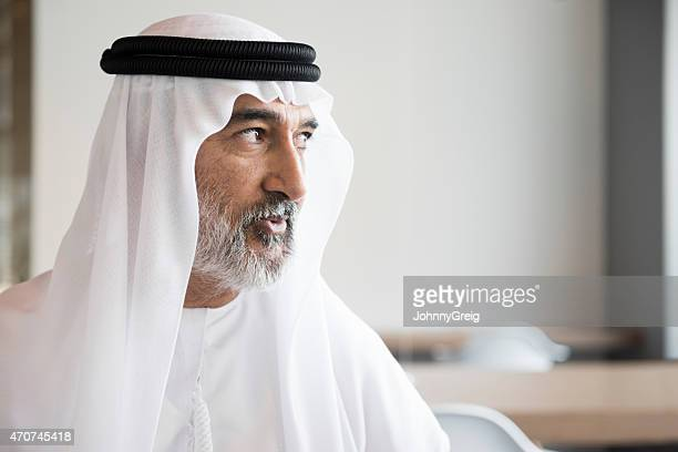 Mature Arab businessman looking away in office
