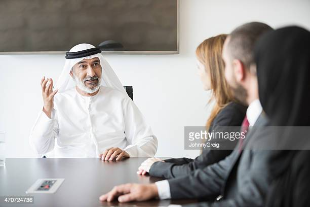 Mature Arab businessman with business colleagues