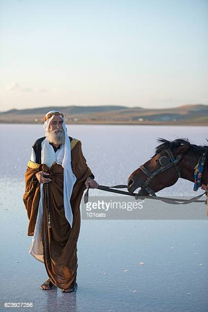 Mature Arabic man with traditional clothes with horse on water