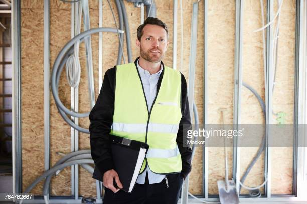 Mature architect with file standing at construction site on sunny day