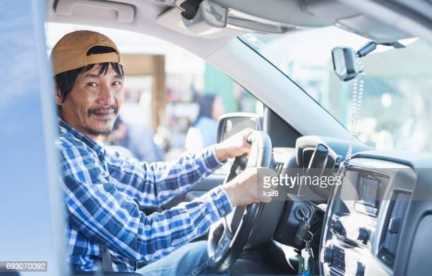 Mature Asian man driving pick-up truck