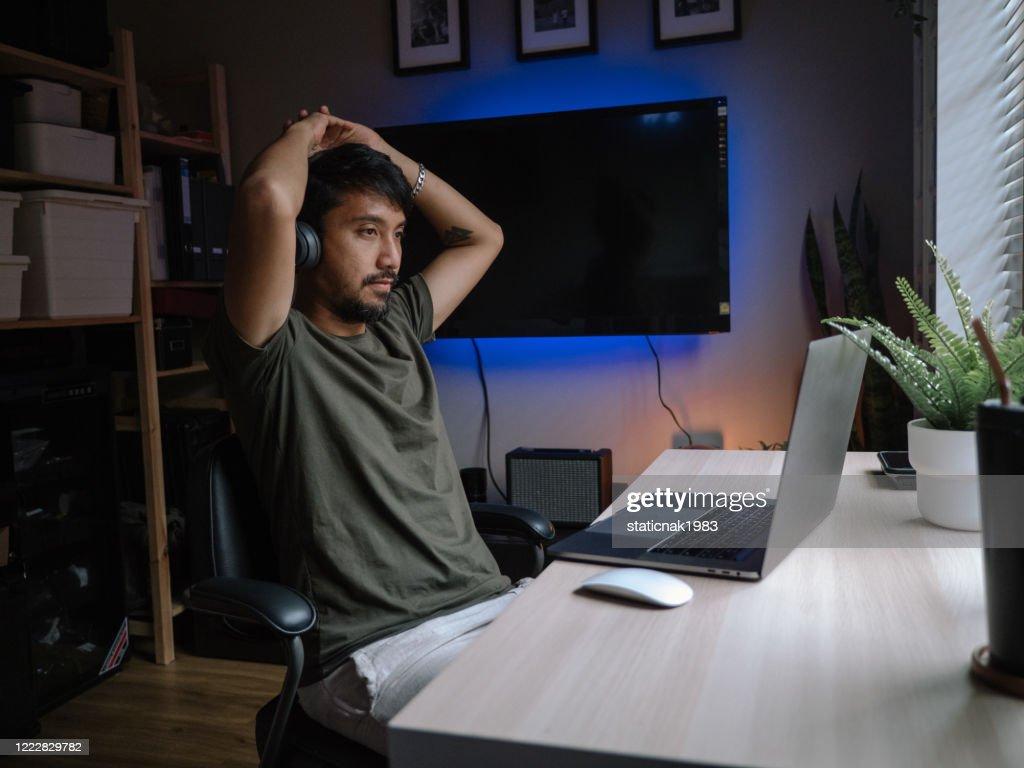 Reife asiatische Mann spielen Online-Spiele auf Laptop-Computer zu Hause. : Stock-Foto