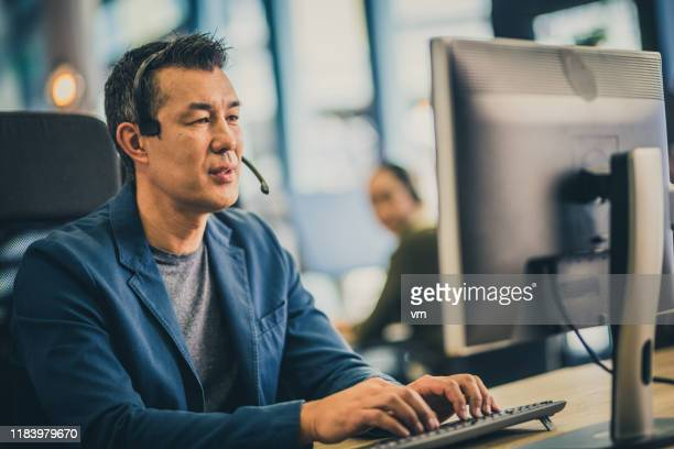 mature asian man working in a call center - customer stock pictures, royalty-free photos & images