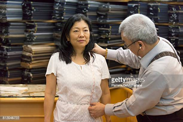 mature asian woman being measured by tailor for handmade suit - fashion hong kong stock photos and pictures