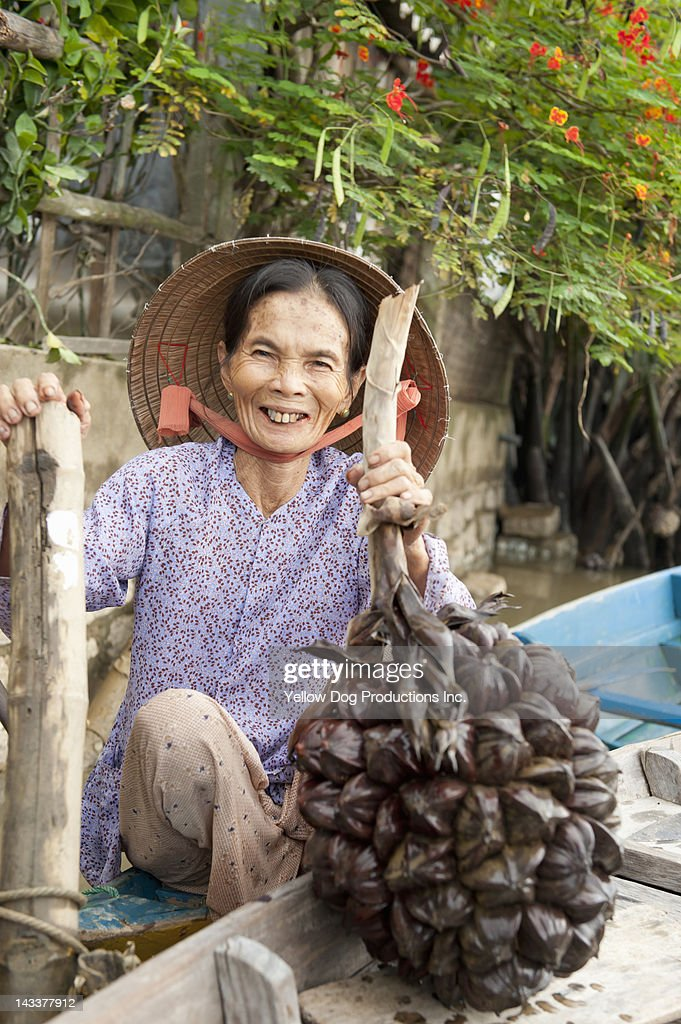 Mature Asian Woman Holding Water Cocunut Stock Photo