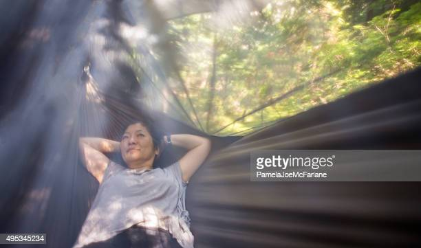mature asian woman relaxing in hanging hammock tent in forest - lech stock pictures, royalty-free photos & images