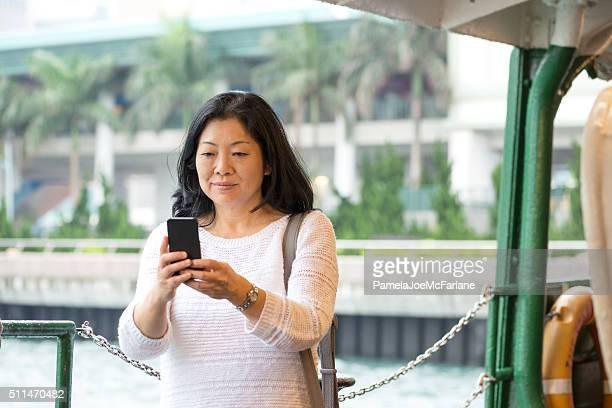 Maduro mujer asiática SMS por teléfono celular mientras Ferry solo