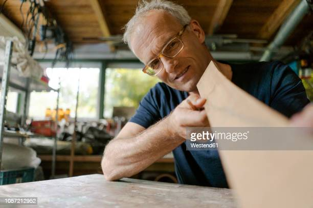 mature at working on wood in his workshop - exactitude photos et images de collection