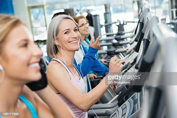 Mature athlete running on treadmill in busy exercise gym
