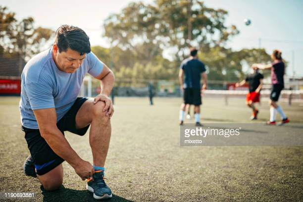 mature athlete tying shoelace on sport field outdoor - soccer competition stock pictures, royalty-free photos & images