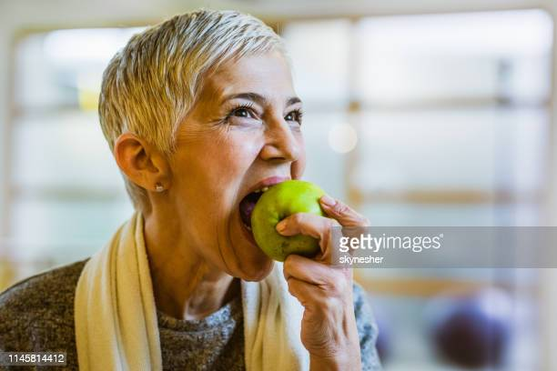 mature athletic woman eating an apple after exercising in health club. - biting stock pictures, royalty-free photos & images