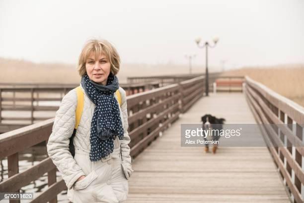 madura atractiva mujer de 50 años de edad, paseando al perro en el paseo marítimo - 50-59 years and women only fotografías e imágenes de stock