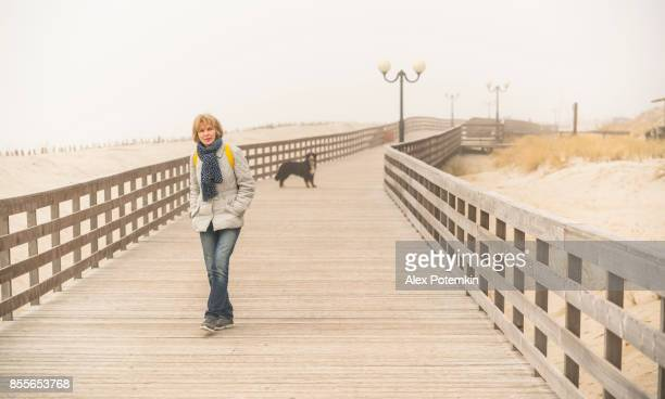 mature attractive 50-years-old woman walking the dog on the boardwalk - approaching stock pictures, royalty-free photos & images