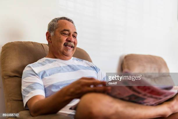 Mature Australian Aboriginal Man Reading a Newspaper at Home