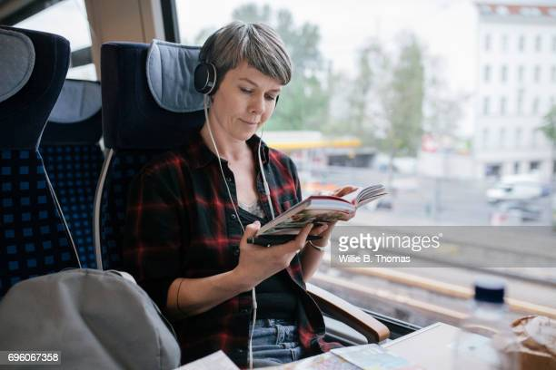Mature Backpacker Reading On Train