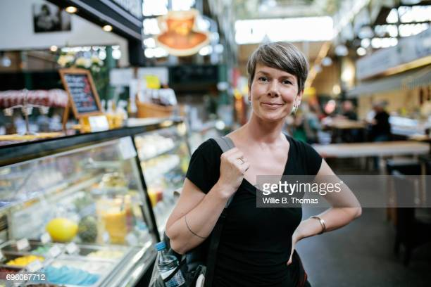 A Mature Backpacker Smiling At An Indoor Market