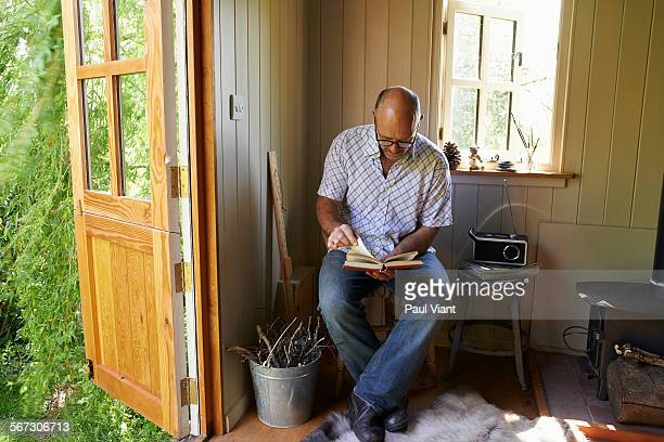 mature bald man 48-52 reading in garden shed