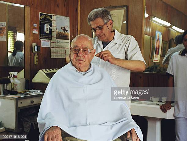 Mature barber cutting senior man's hair