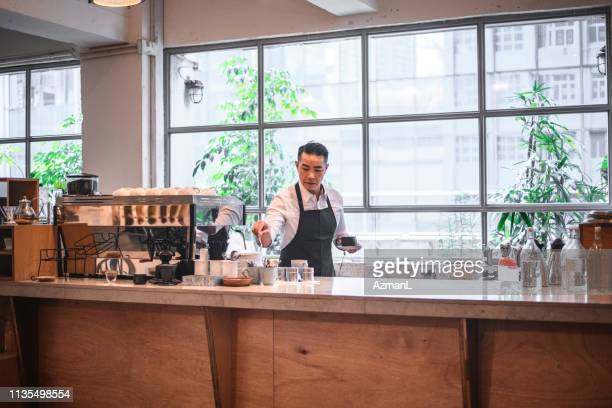 Mature barista holding coffee cup at counter