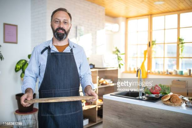 mature bearded man holding wooden tray - serving tray stock pictures, royalty-free photos & images
