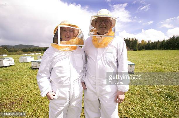 Mature beekeepers wearing protective gear