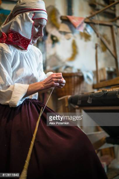 mature belarussian woman wearing the traditional dress spinning next to the vintage loom - belarus stock pictures, royalty-free photos & images