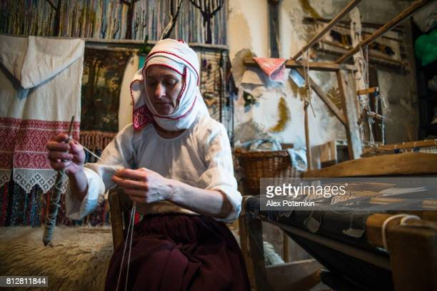 Mature Belarussian woman wearing the traditional dress spinning next to the vintage loom