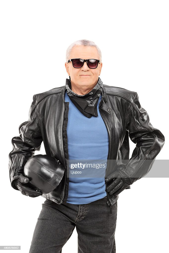 Mature biker in a leather jacket holding a helmet : Stockfoto
