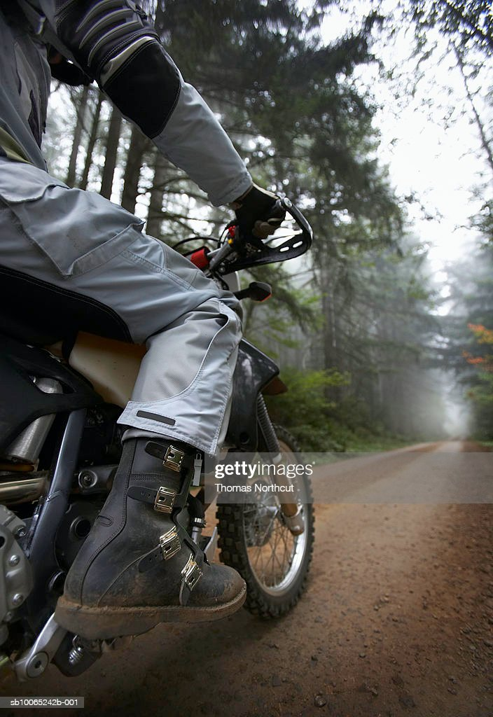 Mature biker riding in forest, low section : Stock Photo