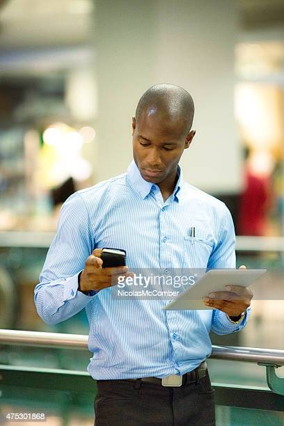 Mature black businessman in mall looking at mobile phone