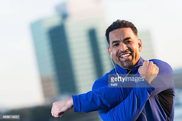 Maduro Hombre negro en la ciudad o hacer ejercicios de estiramiento
