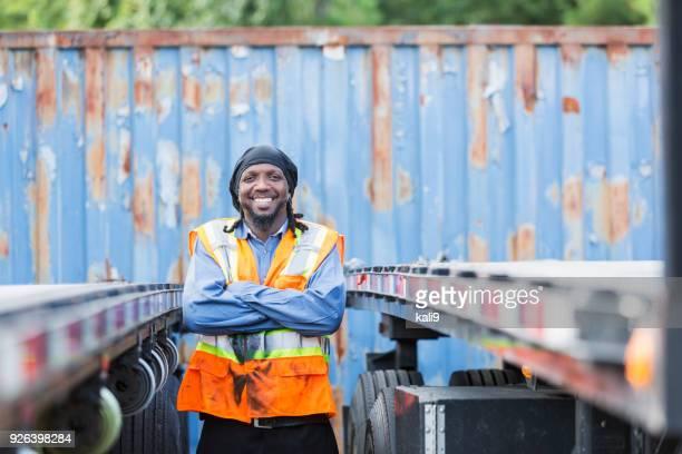 彼のトラックの横にある安全ベストの成熟した黒人男性 - ドゥーラグ ストックフォトと画像