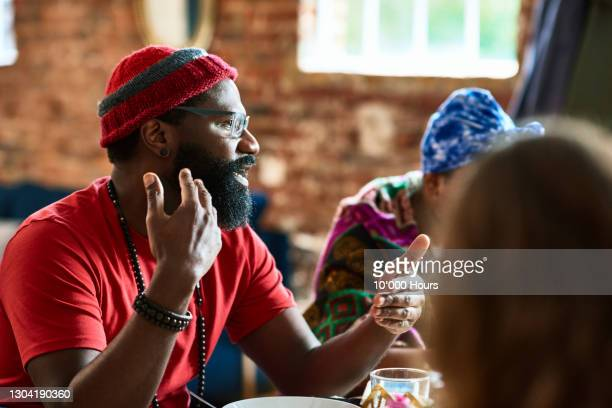 mature black man talking gesturing at lunch table - community stock pictures, royalty-free photos & images