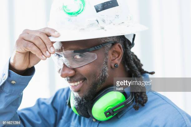 Mature black man wearing hardhat and safety glasses