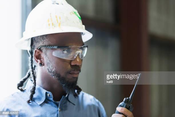 Mature black man wearing hardhat with walkie talkie