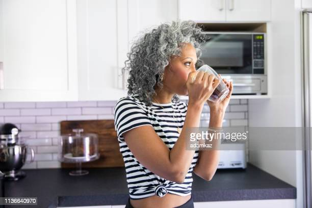 Mature Black woman Drinking Coffee in Bright Modern Kitchen