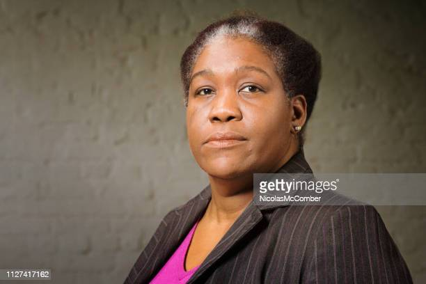 mature black woman in her 50s studio portrait with wall background - one mature woman only stock pictures, royalty-free photos & images