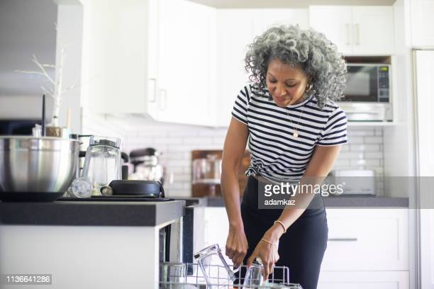 Mature Black Woman Loading Dishwasher