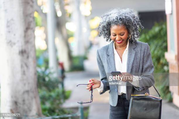 mature black woman texting while walking in city - grey purse stock pictures, royalty-free photos & images