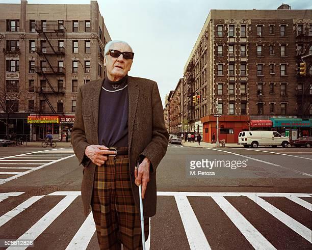 Mature blind man standing on zebra crossing