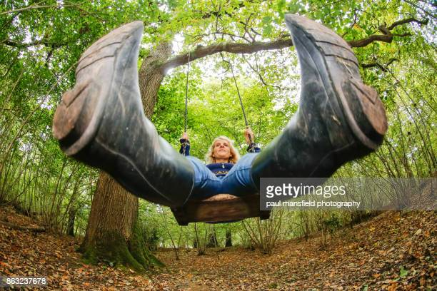 mature blond lady on rope swing - wide angle stock pictures, royalty-free photos & images