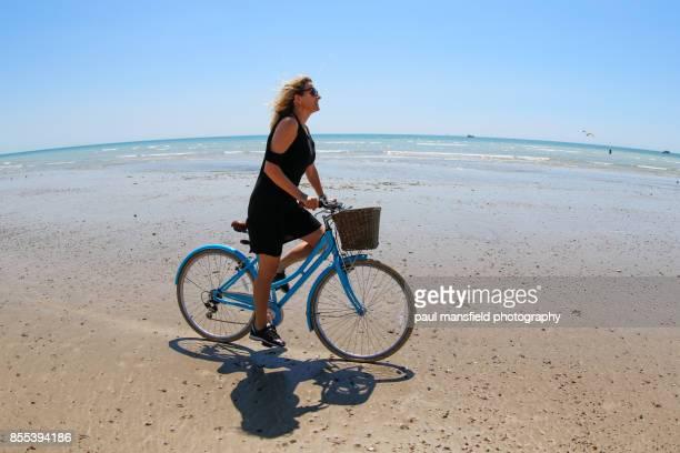 Mature blond lady riding bicycle on sandy beach