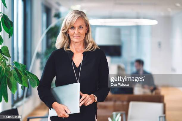 mature blonde businesswoman holding a laptop - adults only stock pictures, royalty-free photos & images