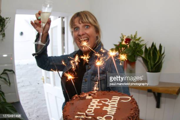 "mature blonde lady holding birthday cake - ""paul mansfield photography"" stock pictures, royalty-free photos & images"