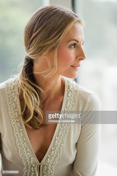 mature blonde woman looking away, portrait - escote fotografías e imágenes de stock